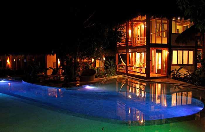 Pranamar villa at night with pool